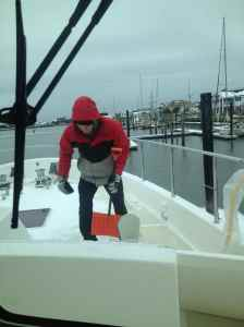 Gary shovels snow on the bow