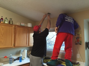 Bradley helps Mike install a light in Mike's kitchen in CO